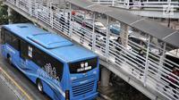 Calon penumpang melintasi jembatan saat hendak menggunakan bus Transjakarta di halte Tosari, Jakarta, Kamis (26/7). Gubernur DKI Jakarta Anies Baswedan mengklaim jumlah penumpang Transjakarta meningkat hingga 10 persen. (Merdeka.com/Iqbal S. Nugroho)