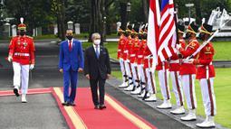 Presiden Indonesia Joko Widodo (kedua kiri) berjalan dengan Perdana Menteri Malaysia Muhyiddin Yassin saat mereka memeriksa penjaga kehormatan dalam pertemuan di Istana Merdeka, Jakarta, Jumat (5/2/2021). Muhyiddin Yasin tiba sekira pukul 10.30 WIB. (Agus Suparto, Indonesian President Palace via AP)