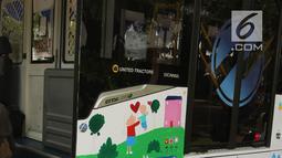 Seorang anak berkebutuhan khusus melukis bus Transjakarta di halaman Balai Kota, Jakarta, Jumat (20/4). Kegiatan tersebut dalam rangka memperingati Hari Kartini. Tema lukisan yang diangkat adalah 'Ibuku Perempuan Tangguh'. (Liputan6.com/Arya Manggala)