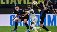 Duel Real Madrid Vs Inter Milan di fase Grup D Liga Champions 2021/22, Kamis (16/9/2021) - Vinicius Jr dikepung Milan Skriniar (kiri) dan Nicolo Barella (kanan). (AFP/Miguel Medina)