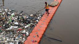 Pekerja kebersihan membersihkan sampah di Sungai Kanal Banjir Barat, Jakarta, Senin (14/11). Hujan yang terjadi di hulu Banjir Kanal Barat mengakibatkan meningkatnya debit air yang disertai sampah. (Liputan6.com/Johan Tallo)