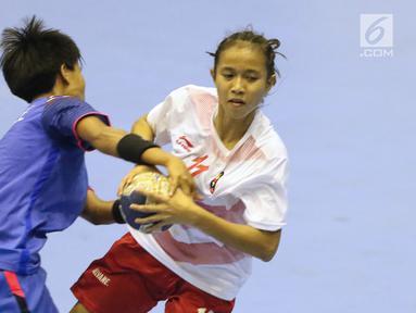 Pemain bola tangan putri Indonesia, Marselina (kanan) berebut bola dengan pemain Thailand pada babak penyisihan grup B Asian Games 2018 di Jakarta, Kamis (16/8). Indonesia kalah 16-34. (Liputan6.com/Helmi Fithriansyah)