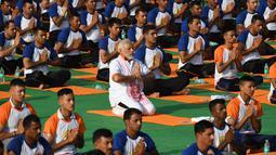 Perdana Menteri India, Narendra Modi berpartisipasi dalam sesi yoga massal pada Hari Yoga Internasional di Dehradun, Kamis (21/6). Modi melakukan gerakan peregangan, membungkuk, dan latihan pernapasan bersama praktisi yoga lainnya. (AFP/PRAKASH SINGH)