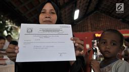 Warga didampingi anaknya menunjukkan tanda bukti pembuatan KIA saat pelayanan Bina Kependudukan di Rusun Petamburan, Jakarta, Rabu (26/6/2019). Pendataan ini melayani warga untuk membuat KTP elektronik, Kartu Identitas Anak (KIA), dan akte kelahiran. (merdeka.com/Iqbal S. Nugroho)