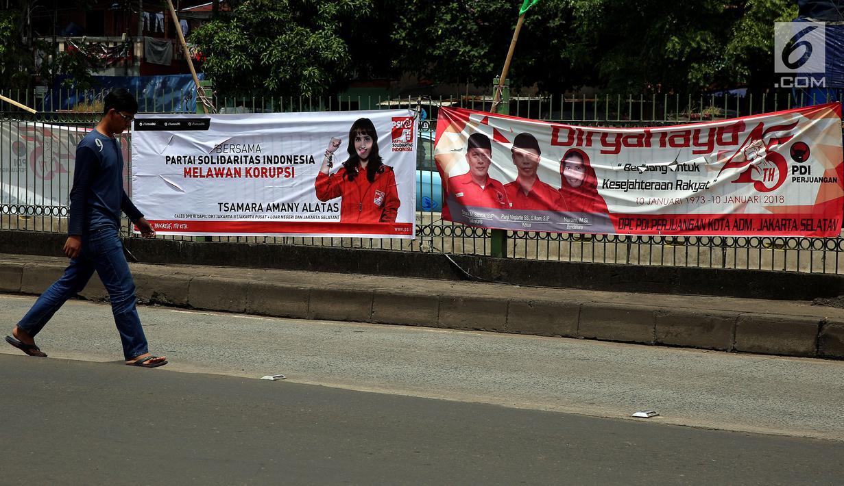 Pejalan kaki berjalan di depan spanduk partai politik yang terpampang di Jalan Sultan Agung, Manggarai, Jakarta, Selasa (16/1). Memasuki 2018, parpol berlomba mengambil hati rakyat dengan berbagai janji terpampang di spanduknya. (Liputan6.com/JohanTallo)