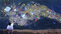 Seorang pria memancing di pantai Laut Tengah di Beirut, Lebanon di antara berbagai sampah plastik. (AP)
