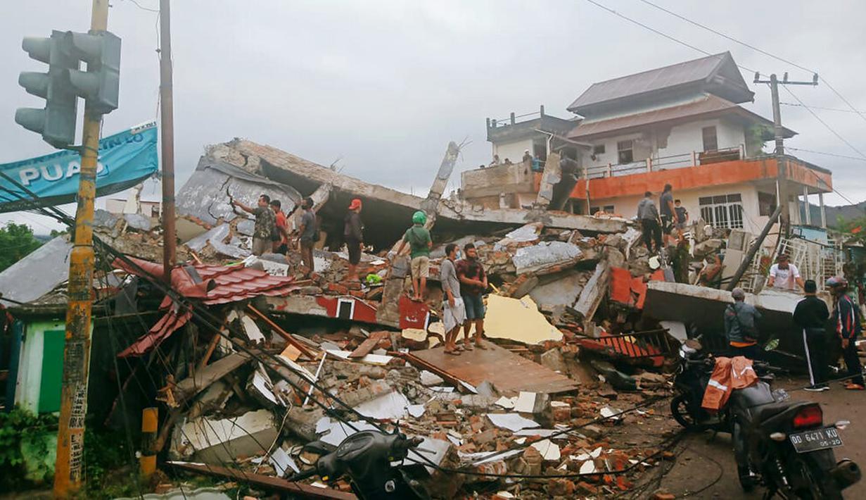 Warga memeriksa bangunan yang rusak akibat gempa di Mamuju, Sulawesi Barat, Indonesia, Jumat (15/1/2021). Sejumlah rumah dan bangunan di Mamuju roboh akibat gempa dengan berkekuatan 6,2 skala Richter yang berpusat di timur laut Majene. (AP Photo/Rudy Akdyaksyah)
