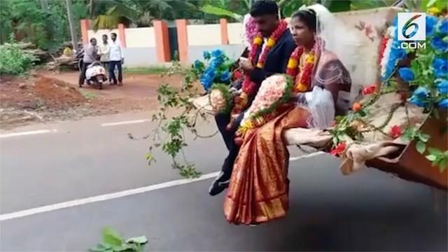 Setelah mengucapkan janji suci pernikahan, pengantin pria di Puttur, India, membawa pulang istrinya menggunakan mobil buldozer lengkap dengan hiasan bunga.