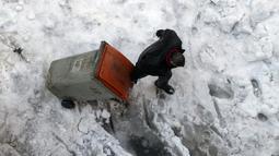 Seorang pria menyeret wadah sampah melalui salju dan es di Madrid, Spanyol, Senin (11/1/2021). Ibu kota Spanyol itu berusaha bangkit kembali setelah menghadapi badai salju terburuk dalam 50 tahun terakhir yang melumpuhkan sebagian besar wilayah Spanyol tengah selama akhir pekan (AP Photo/Paul White)
