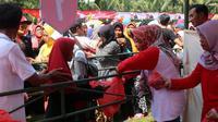 Bupati Purbalingga, Dyah Hayuning Pratiwi membagikan sembako gratis dalam pasar murah di Muli Kecamatan Karangmoncol. (Foto: Liputan6.com/Dinkominfo PBG/Muhamad Ridlo)
