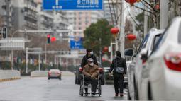 Warga mengenakan masker berjalan di sebuah jalan di Wuhan di provinsi Hubei tengah China (3/3/2020). Sejauh ini, total 80.026 kasus virus corona terkonfirmasi di wilayah China daratan. (AFP/STR)