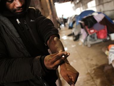 Seorang pria menggunakan heroin di bawah jembatan yang menjadi pusat penggunaan heroin di Kensington, Philadelphia (24/1). Menurut DAE Amerika Serikat, penggunaan heroin telah berlipat ganda di seluruh negeri sejak 2010. (Spencer Platt/Getty Images/AFP)