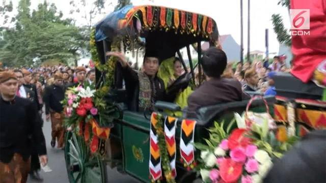 Pada kirab resepsi Kahiyang-Bobby dari atas kereta kencana Presiden Jokowi membagikan suvenir pernikahan kepada warga.