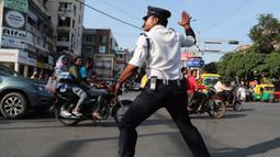 Seorang polisi lalu lintas India, Ranjeet Singh arus kendaraan bermotor di persimpangan yang sibuk di Indore pada 18 November 2019. Singh yang berusia 40 tahun ini selama sepuluh tahun terakhir mengatur lalu lintas sambil menarikan gaya ikonik milik Michael Jackson 'moonwalk.' (AP/Aijaz Rahi)