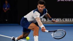 Petenis Serbia, Novak Djokovic berusaha mengembalikan bola ke arah petenis Korea, Hyeon Chung pada ajang Australia Terbuka 2018 di Melbourne,  (22/2/2018). Djokovic kalah 6-7, 5-7, 6-7. (AFP/Saeed Khan)