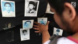 Aktivis melihat foto para korban HAM saat aksi Kamisan ke-538 di depan Istana Negara, Jakarta, Kamis (17/5). Aksi Kamisan tersebut sekaligus memeringati 20 tahun reformasi. (Liputan6.com/Immanuel Antonius)