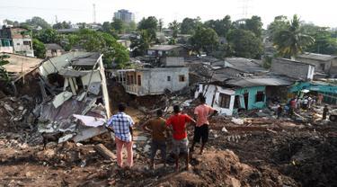 Warga Sri Lanka mengamati rumah mereka yang rusak tertimbun gundukan sampah yang longsor di Meetotamulla, dekat ibukota Kolombo, Minggu (16/4). Sedikitnya 23 orang tewas akibat tanah longsor di tempat pembuangan sampah tersebut. (ISHARA S. KODIKARA/AFP)