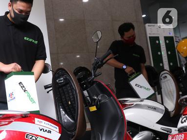 Petugas menguji coba penukaran baterai sepeda motor listrik di halaman kantor Ditjen Ketenagalistrikan ESDM, Jakarta, Senin (31/8/2020). Stasiun Penukaran Baterai Kendaraan Listrik Umum (SPBKLU) ini diharap dapat meningkatkan permintaan listrik dari energi baru terbarukan (Liputan6.com/Angga Yuniar)