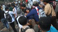Sejumlah pelajar menggotong rekan mereka yang terluka dalam demonstrasi di belakang Gedung DPR, Palmerah, Jakarta, Rabu (25/9/2019). Pelajar bahu membahu membantu rekan mereka yang terluka dalam demonstrasi. (Liputan6.com/Angga Yuniar)