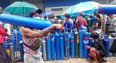 Seorang pria membawa tabung oksigen di luar pabrik oksigen Naing di zona industri South Dagon di Yangon, Myanmar, Rabu (28/7/2021). Myanmar saat ini dilanda lonjakan jumlah kasus COVID-19 dan kematian yang sangat membebani infrastruktur medis negara itu. (AP Photo)