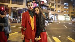 Pasangan mengenakan kostum Halloween berdiri di sebuah jalan di Hong Kong, Kamis (31/10/2019). Polisi Hong Kong bersiap untuk berjaga unjuk rasa Kamis malam, yang akan menguji peraturan larangan pemerintah untuk menutup wajah yang diperkenalkan bulan ini. (AP Photo/Kin Cheung)
