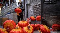 Seorang pekerja memasang lentera tradisional Tiongkok di sepanjang gang menjelang Tahun Baru Imlek di Beijing, China, 2 Februari 2021. Imlek tahun ini jatuh pada tanggal 12 Februari 2021. (NOEL CELIS/AFP)