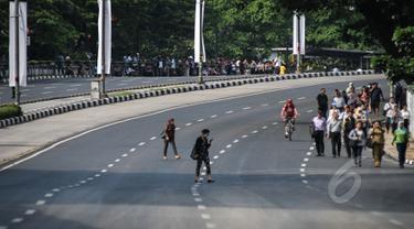 Sejumlah karyawan berjalan kaki untuk menuju kantornya di sekitar kawasan Bundaran HI, Jakarta, Rabu (22/4/2015). Sejumlah jalan utama di Jakarta ditutup total untuk sementara waktu terkait puncak Konferensi Asia-Afrika (KAA). (Liputan6.com/Faizal Fanani)