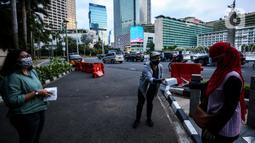 Suasana pembagian takjil kepada pejalan kaki di Kawasan Bundaran HI, Jakarta, Selasa (20/4/2021). Kegiatan berbagi takjil yang digagas oleh Pewarta Foto Indonesia Jakarta (PFIJ) ini dilaksanakan setiap hSelasa dan Jumat selama bulan Ramadhan sebagai bentuk solidaritas. (Liputan6.com/JohanTallo)