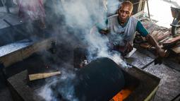 Pekerja memanggang biji kopi melalui metode tradisional di sebuah pabrik di Banda Aceh, Aceh, Rabu (3/3). (CHAIDEER MAHYUDDIN/AFP)