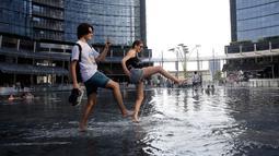 Warga mendinginkan diri dengan bermain di air mancur saat gelombang panas menerjang Eropa di Milan, Italia, Rabu (24/7/2019).  Gelombang panas yang melanda Eropa diperkirakan akan semakin meningkat. (AP Photo/Luca Bruno)
