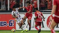 Gelandang Mitra Kukar, Arif Suyono, berebut bola dengan bek Persija Jakarta, Rezaldi Hehanussa, pada laga Liga 1 di SUGBK, Jakarta, Minggu (9/12). Persija menang 2-1 atas Mitra. (Bola.com/Yoppy Renato)