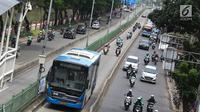 Pengendara motor melaju di belakang bus Transjakarta di kawasan Pasar Rumput, Jakarta, Rabu (20/2). Sekitar 510 CCTV akan dipasang di 225 halte Transjakarta di Ibu Kota untuk menerapkan tilang online atau E-Tilang. (Liputan6.com/Immanuel Antonius)