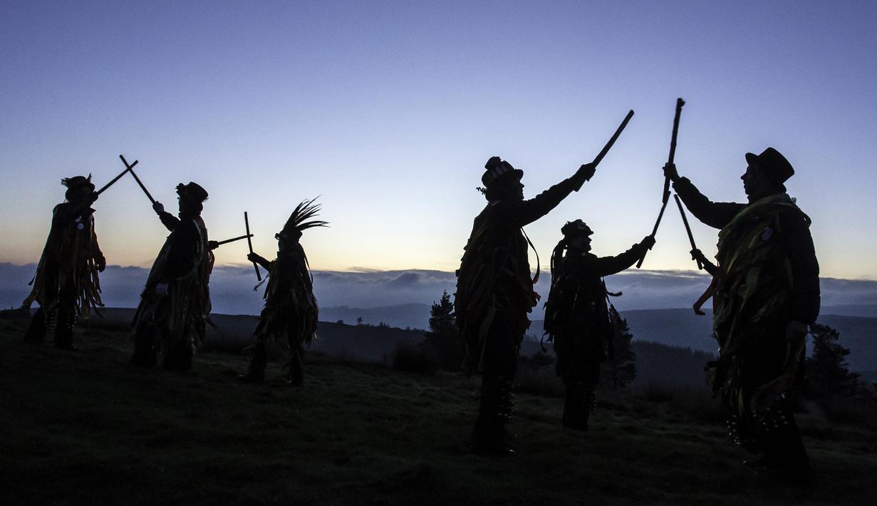 Anggota Powderkeg Morris Dancers menari di atas Windgather Rocks di High Peak di Derbyshire sebelum matahari terbit (1/5). Mereka melakukan tarian tahunan sebagai bagian dari festival Celtic kuno. (AFP Photo/Lindsey Parnaby)