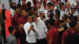 Presiden Joko Widodo berselfie saat menghadiri Silaturahmi Nasional Pemerintahan Desa se-Indonesia di Jakarta, Rabu (10/4). Presiden  Jokowi mengatakan akan terus menaikkan jumlah dana desa serta memudahkan sistem laporan pertanggung jawabannya. (Liputan6.com/Angga Yuniar)