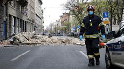Seorang pemadam kebakaran Kroasia berjalan melewati puing-puing setelah gempa di jalan-jalan pusat kota Zagreb (22/3/2020). Lindu merusak sejumlah gedung dan membuat banyak mobil hancur karena terjangan batu. (AFP/Damir Sencar)