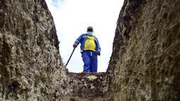 Seorang penggali makam melihat ke dalam kuburan di Pemakaman Motherwell di Port Elizabeth, Afrika Selatan pada 4 Desember 2020. Menteri Kesehatan Afrika Selatan, Zweli Mkhize pada Rabu (9/12/2020) mengumumkan negara itu sekarang sedang mengalami gelombang kedua Covid-19. (AP Photo/Theo Jeftha)