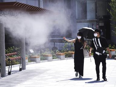 Seorang pria dan wanita mengenakan masker untuk mencegah penyebaran Covid-19 di bawah titik kabut dingin di Tokyo (12/8/2020). Menurut Badan Meteorologi Jepang, cuaca panas telah ditetapkan dengan suhu naik lebih dari 34 derajat Celcius (93,2 derajat Fahrenheit) di Tokyo. (AP Photo/Eugene Hoshiko)