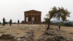 Turis saat mengunjungi Lembah Kuil selama gelombang panas di dekat Agrigento, Sisilia, Italia (11/8/2021). Gelombang panas yang berkelanjutan akan berlangsung hingga akhir pekan dengan suhu diperkirakan mencapai lebih dari 40 derajat Celcius di banyak bagian dari Italia. (AP Photo/Salvatore Cavalli)