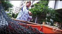 Seorang warga tampak memberikan makan lelenya dengan pakan khusus ikan, Jakarta, Selasa (19/8/2014) (Liputan6.com/Faizal Fanani)