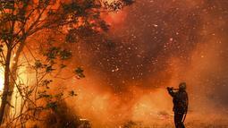 Seorang petugas pemadam kebakaran memadamkan api di Cordoba, Argentina (12/10/2020). Kebakaran hutan telah menghancurkan ribuan hektar di provinsi Cordoba, Argentina tahun ini, di tengah kekeringan dan suhu tinggi. (AP Photo/Nicolas Aguilera)