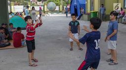 Anak-anak pencari suaka bermain bola voli di halaman bekas Markas Kodim di Kalideres, Jakarta, Selasa (16/7/2019). Sejak Kamis (11/7) para pencari suaka dipindahkan dari di pinggir jalan dan trotoar di kawasan Kebon Sirih ke bekas Markas Kodim di Kalideres . (Liputan6.com/Helmi Fithriansyah)