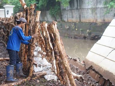 Petugas Sudin SDA Jakarta Selatan memperbaiki tanggul Kali Krukut yang jebol di Jalan Perumahan Kemang Jaya, Bangka, Jakarta, Rabu (8/1/2020). Tanggul jebol akibat tak kuat menahan derasnya air kiriman dari hulu serta hujan deras yang mengguyur kawasan tersebut. (Liputan6.com/Immanuel Antonius)