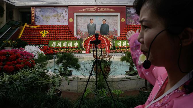 Pemandu memberi isyarat di depan potret pemimpin Korea Utara, Kim Il Sung dan Kim Jong Il pada pameran bunga 'Kimjongilia' di Pyongyang, Kamis (14/2). Korea Utara menggelar festival bunga merayakan ulang tahun mendiang ayah Kim Jong-un. (Ed JONES/AFP)