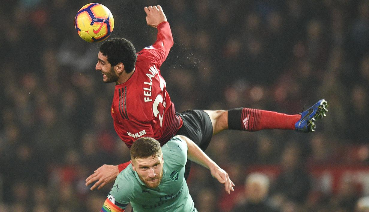 Gelandang Manchester United, Marouane Fellaini, duel udara dengan bek Arsenal, Shkodran Mustafi pada laga Premier League di Stadion Old Trafford, Manchester, Rabu (5/12). Kedua klub bermain imbang 2-2. (AFP/Oli Scarff)
