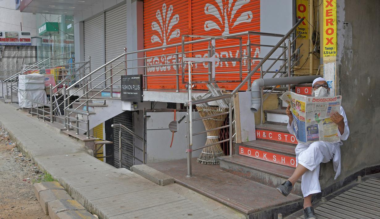 Seorang pria membaca koran di depan toko-toko yang tutup di area komersial saat pemberlakukan lockdown di Bangalore, Rabu (15/7/2020). Pusat IT India, Bangalore, kembali memberlakukan lockdown selama seminggu dimulai dari 14 Juli 2020 setelah adanya lonjakan kasus Covid-19. (Manjunath Kiran/AFP)