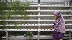 Warga melintas di salah satu gang kampung hijau di kawasan Malakasari, Jakarta, Sabtu (15/9). Tingginya kesadaran masyarakat akan pentingnya tumbuhan membuat kawasan tersebut terlihat asri dan dipenuhi berbagai tanaman. (Liputan6.com/Immanuel Antonius)