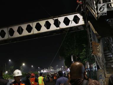 Pekerja berusaha menurunkan potongan rangka utama Jembatan Penyeberangan Orang Pasar Minggu, Jakarta, Sabtu (6/4). Proses pembongkaran JPO Pasar Minggu ini akan berlangsung hingga 7 April mendatang. (Liputan6.com/Helmi Fithriansyah)
