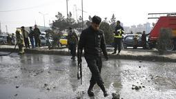 Polisi memeriksa lokasi ledakan bom di Kabul (2/2/2021).  Dua orang tewas ketika ibu kota Afghanistan diguncang serangkaian bom mobil pada jam sibuk, kata para pejabat, sementara seorang polisi kendaraan menjadi sasaran dalam serangan di utara Kabul. (AFP/Bangun Kohsar)
