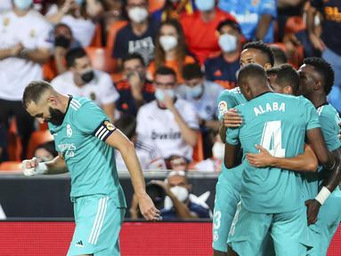 Penyerang Real Madrid Vinicius Junior berselebrasi dengan rekan setimnya setelah mencetak gol ke gawang Valencia pada lanjutan La Liga di Stadion Mestalla, Senin (20/9/2021) dini hari WIB. Real Madrid menang 2-1 secara dramatis atas Valencia. (AP Photo/Alberto Saiz)