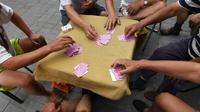Sekelompok pria bersiap bermain kartu remi di trotoar di luar gedung apartemen di Beijing, China (10/8). Seperti kita kenal sekarang, satu pak kartu remi berisi 52 lembar. (AFP Photo/Greg Baker)